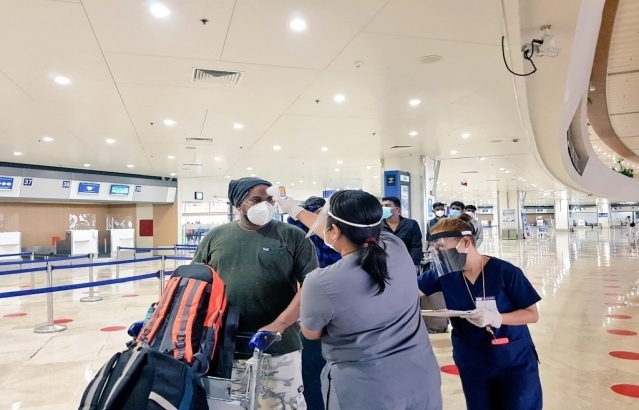 Passenger of Air India AI 1309 undergoes a thermal scan by a health personnel at the Ninoy Aquino International Airport in Manila on 10 July 2020.